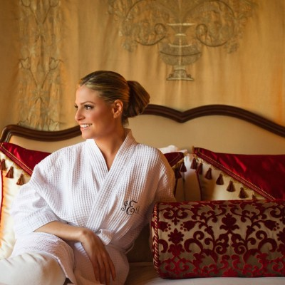 woman lounging in large bed with bathrobe