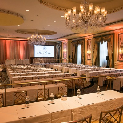 meeting space with long tables and chandeliers during the day