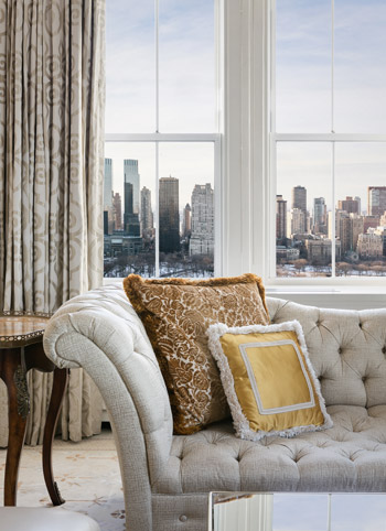 Couch with pillows next to window with city view