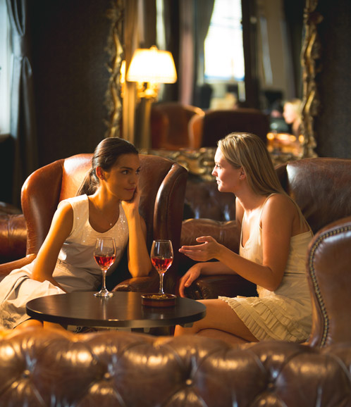 Two women in lounge drinking wine