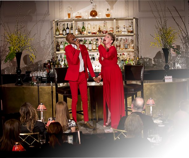 Two people in red suits singing
