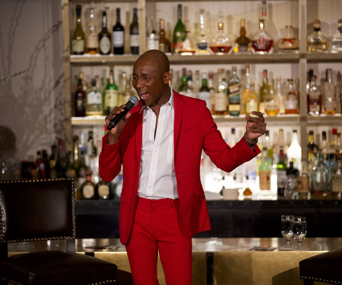 singer and entertainer wearing red suit in front of bar