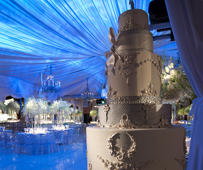 large wedding cake with reception venue lit in blue