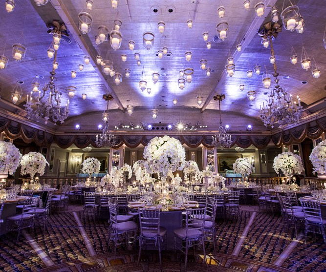 Event space set up for wedding with floral centerpieces and purple lighting