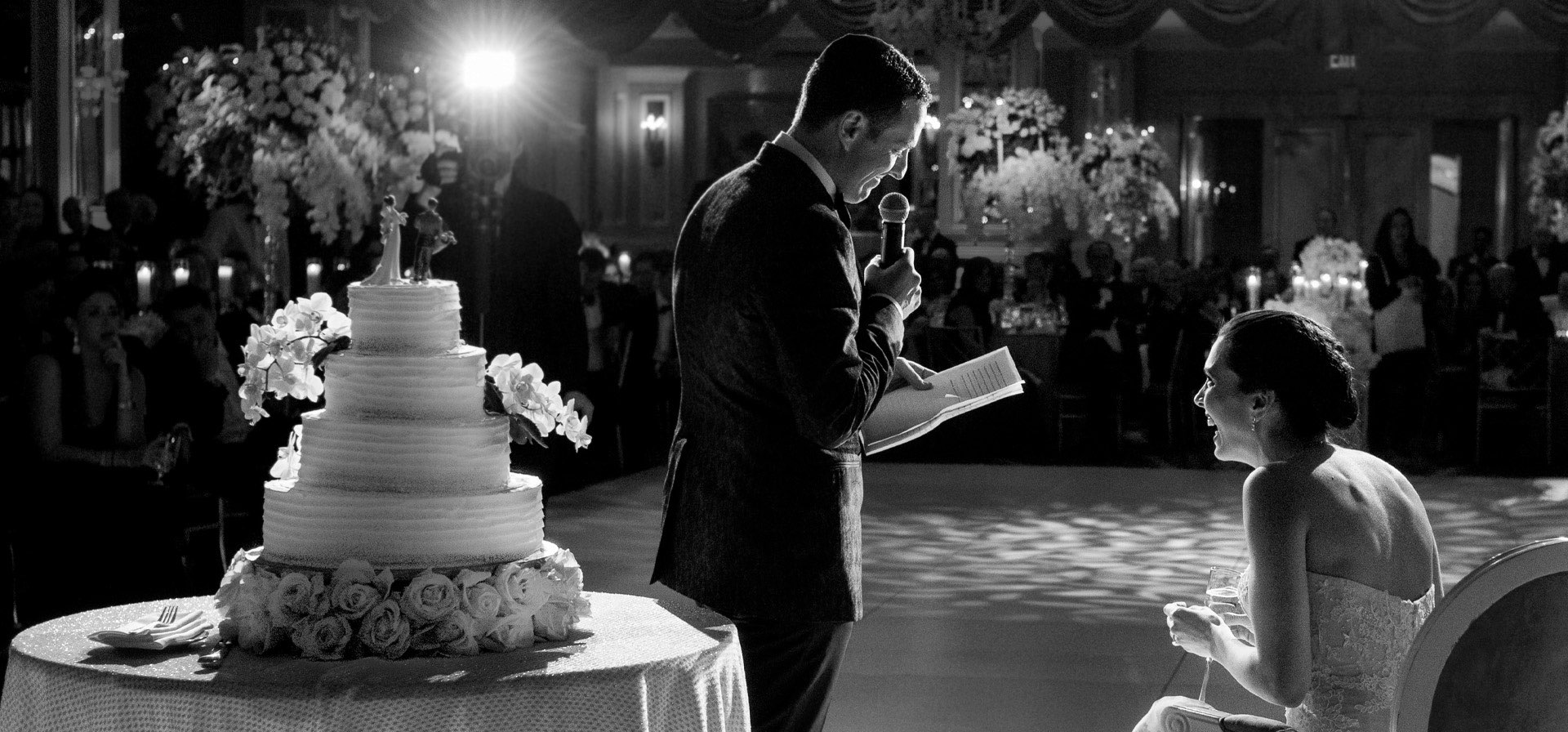 Groom reading to bride in reception party