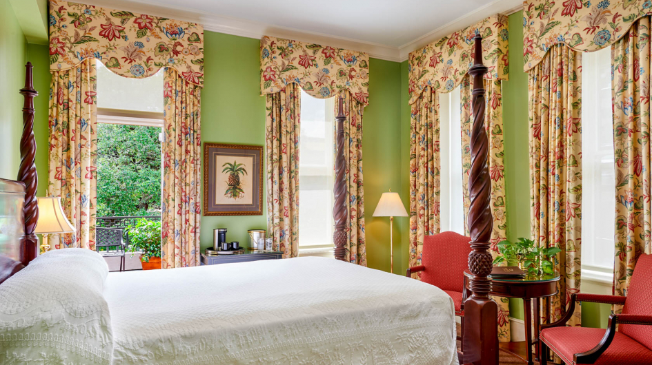 room with bed green wall paper and 4 windows