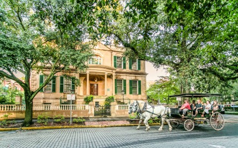 horse drawn carriage ride in front of yellow building