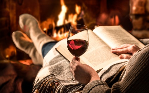 woman reading by the fireplace with a glass of wine