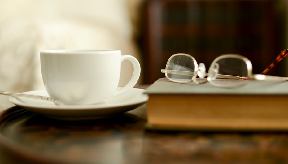a mug next to eyeglasses on top of a book