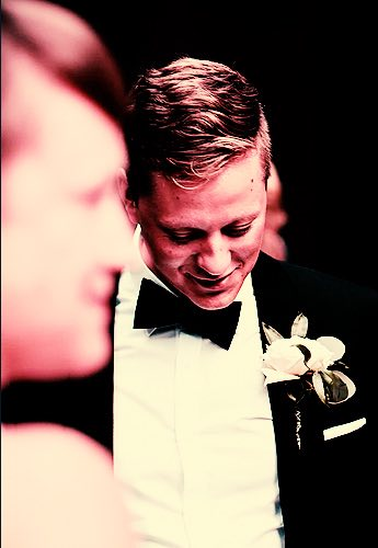 A groom in a tux smiling looking towards the ground