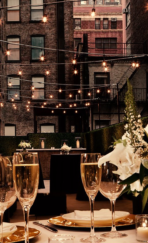 glasses of champagne sitting on a dining table on an outdoor terrace area with string lights