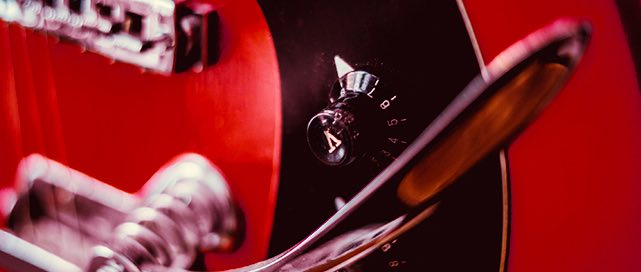 close up of the tuning dial on a red electric guitar