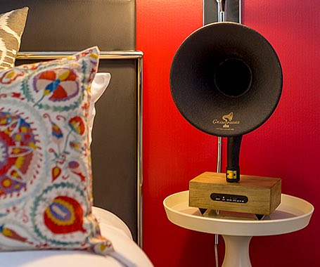 a vintage trumpet speaker on a nightstand next to a bed