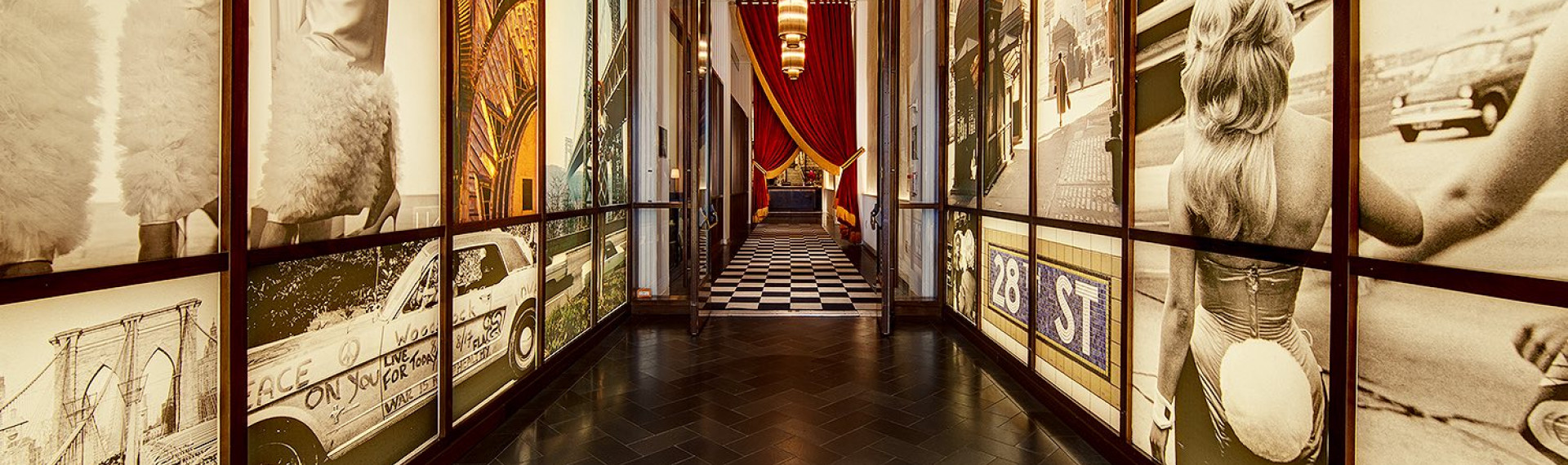 a hallway with large murals on the walls and double glass doors leading to a black and white checkered floor with two large red curtains gathered at the side