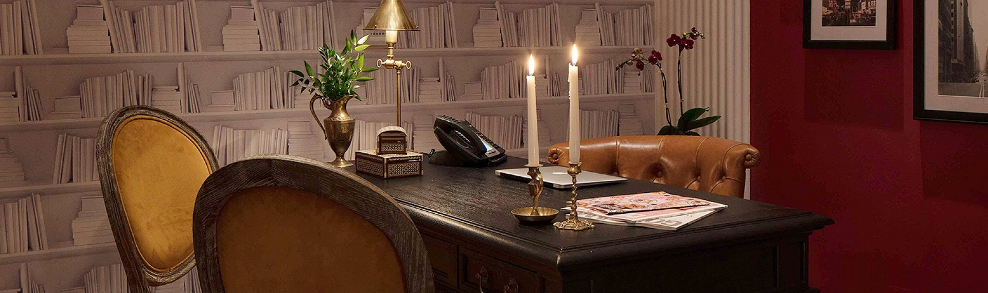 office desk with brown chairs, two lit candlesticks, and white bookcase wallpaper