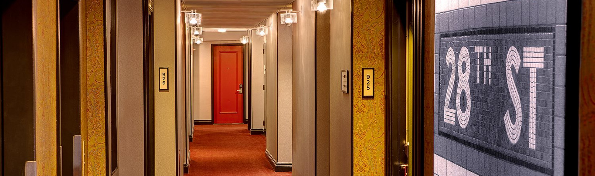 hallway of hotel rooms with gold patterned walls and red doors