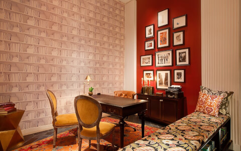 office space with a wood desk, brown leather chair, two mustard chairs, patterned bench, red wall with picture frames, and wall with white bookcase wallpaper