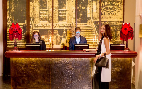 A well dressed woman checking into her hotel at the reception desk with two employees working on the computer behind the counter