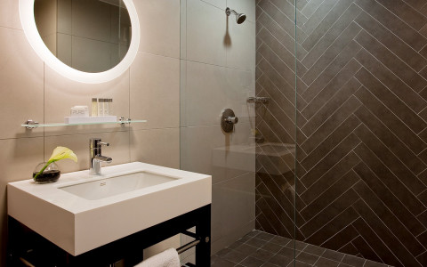 bathroom area with a glass walk in shower, gray tiles, large white sink and a circular illuminated mirror
