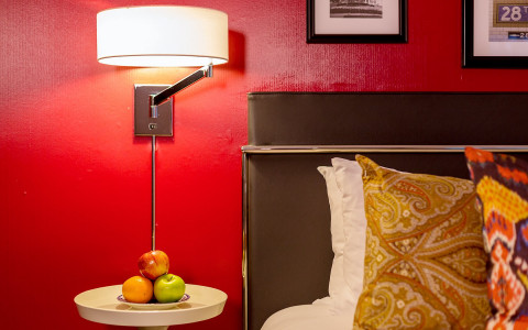 a bedside table with a plate of apples and an overhead lamp next to a bed