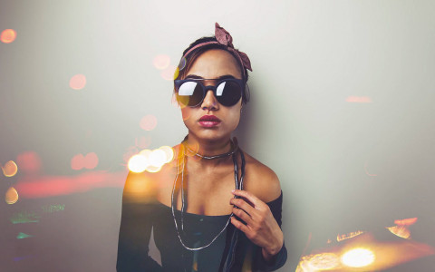a woman wearing sunglasses, a bandana, and a long necklace with a straight face and specks of light around her
