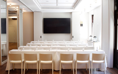 four rows of conference chairs and tables draped with white tablecloths facing a large tv monitor