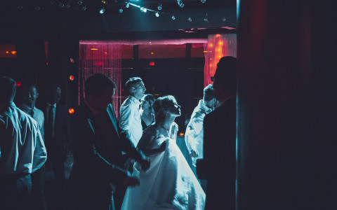 a spotlight shines on a bride and her guests as they dance on the dance floor at the reception