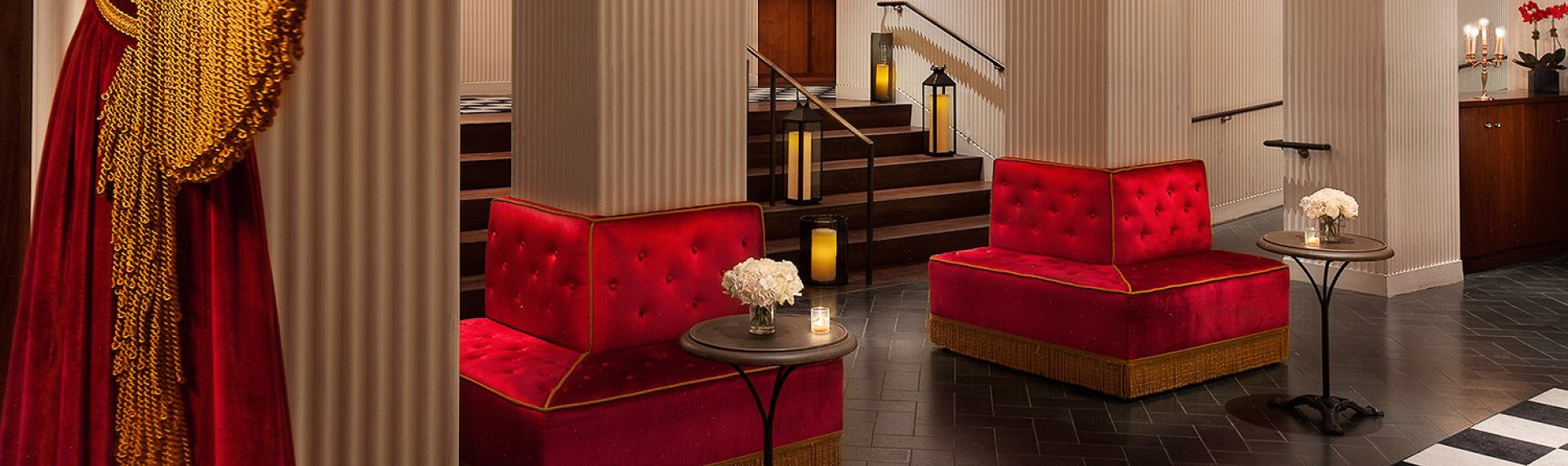 lobby area with red couches connected to columns with gold fringe accents and candle lanterns and other lights around the room