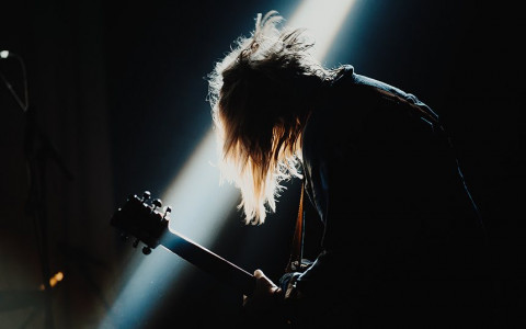 A dark image of a man playing the guitar with the spotlight shining behind him