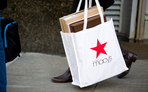 A woman holding a macy's shopping bag