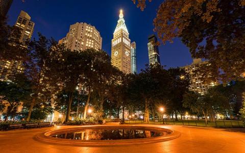 A circular pond in madison square park lit up at night surrounded by trees with a view of buildings lit up in the distance