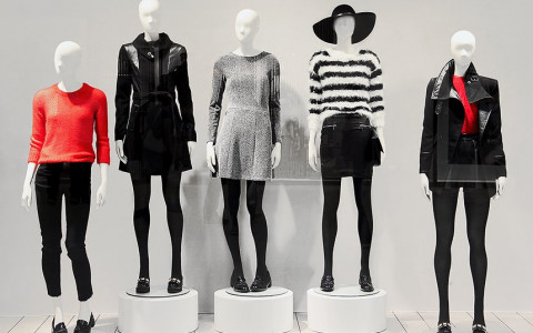 five mannequins dressed in variations of black, white, and red on display at a museum