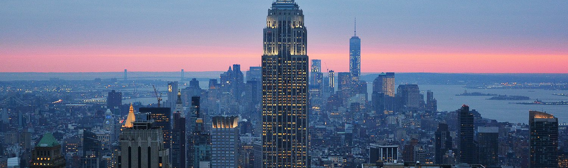 the tall empire state building surrounded by other buildings with a light blue and pink sky in the distance