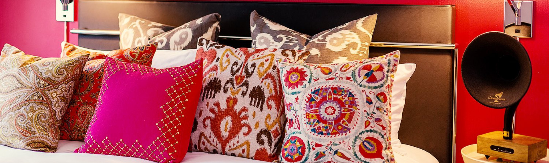 Red, pink, and brown decorative patterned pillows on a bed with a black headboard against a red wall