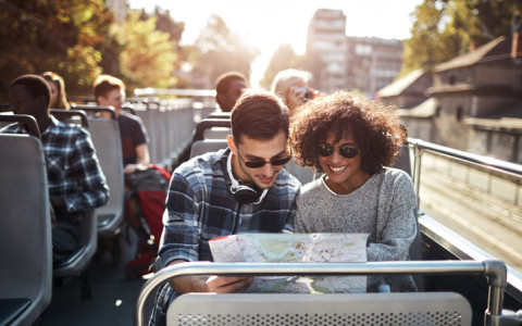 couple on double decker bus tour holding map