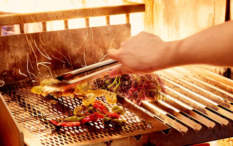 person grilling meat and veggies