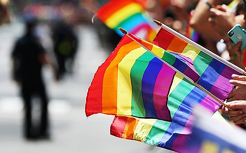 people waving rainbow flags at a parade