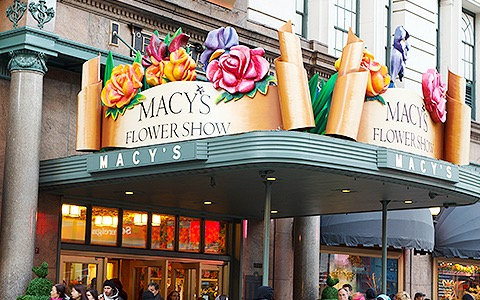 a macy's flower show sign on top of an awning outside the store