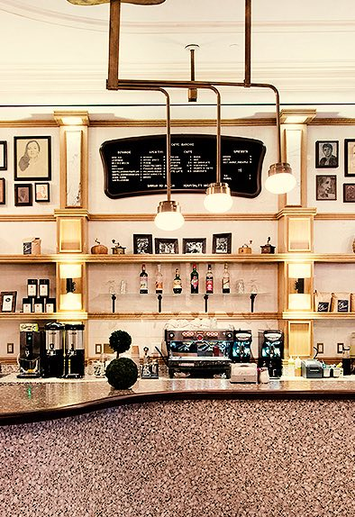 a coffee shop counter with gold accents and hanging lights