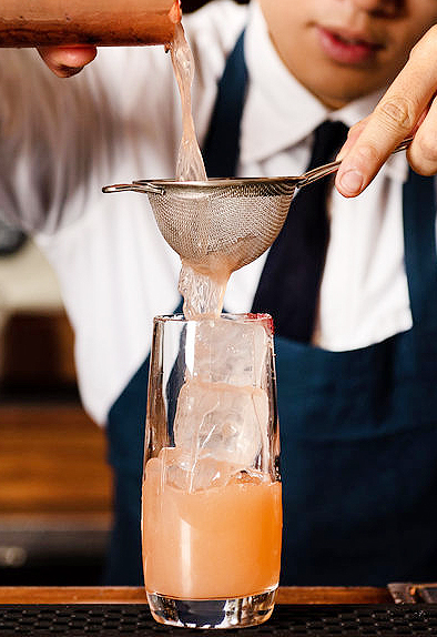 a bartender making a cocktail at the bar