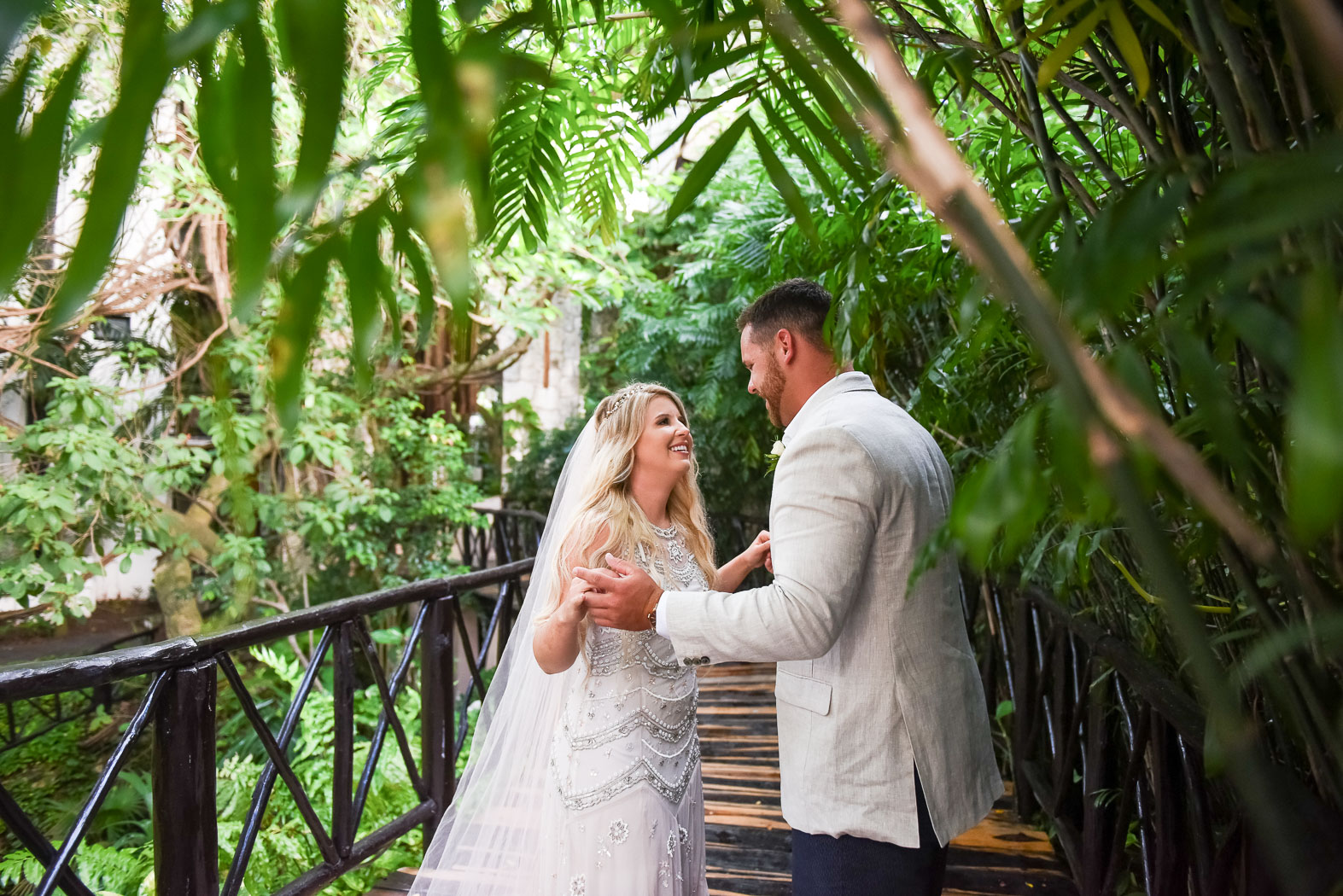 a couple in their wedding attire surrounded by greenery outside