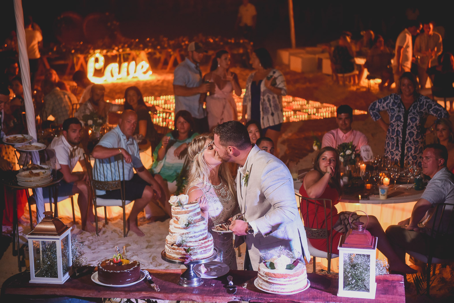 A just married couple kissing next to a cake