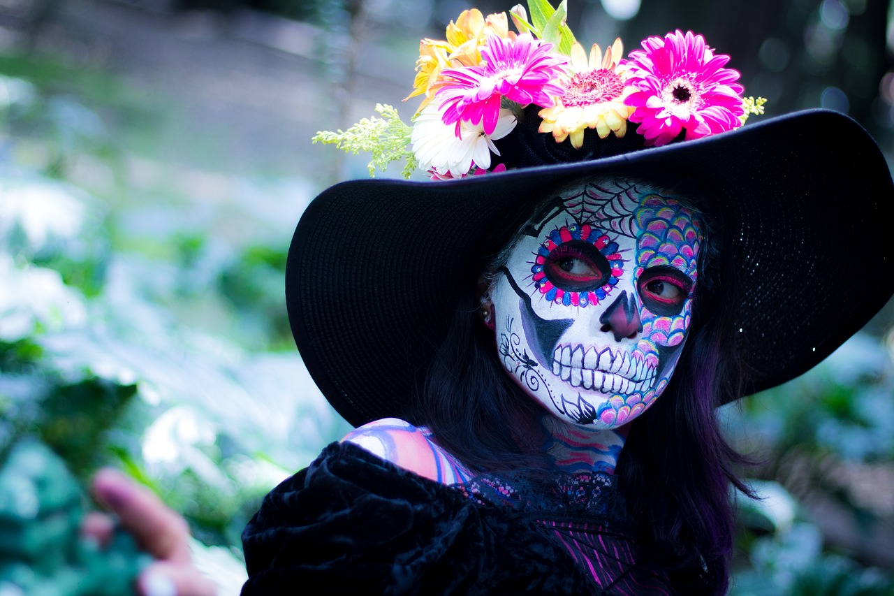 Woman in elaborate Day of the Dead skull face paint and flower hat