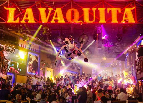 Interior of La Vaquita bar with people dancing and strobe lights