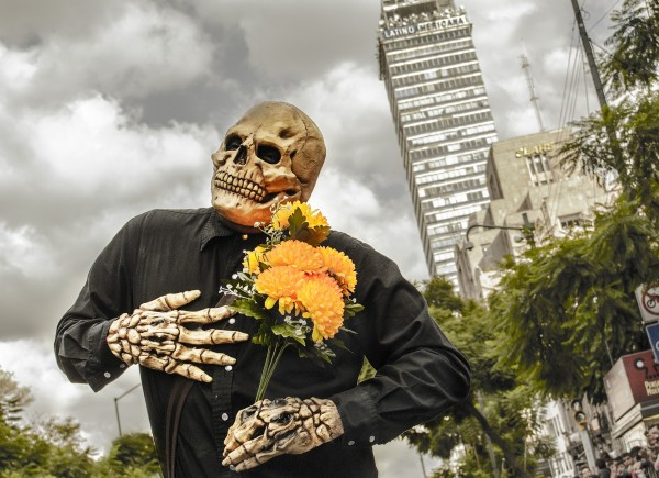 Man outside in city wearing skeleton costume and holding flower for Day of the Dead