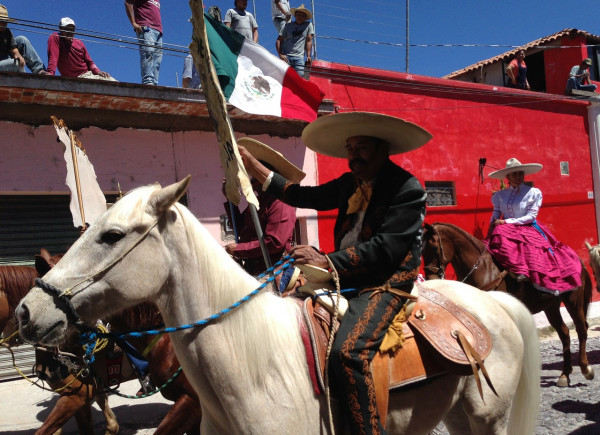 Man on horseback carrying Mexican flag in parade