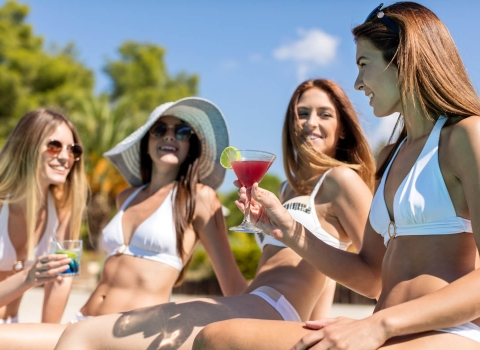 Four adult females in white bikinis drinking cocktails