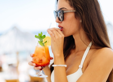 Adult female in white bikini drinking a cocktail