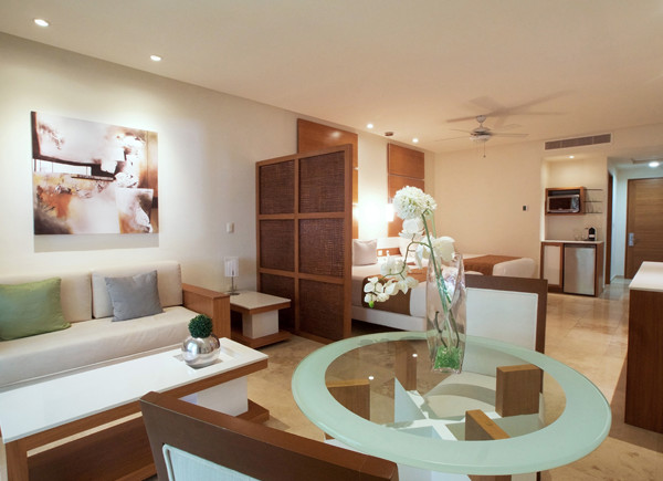 Junior Suite features a white sofa, table for two and two double beds