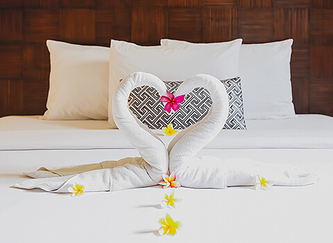 A bed made with white bedding and towel swans kissing